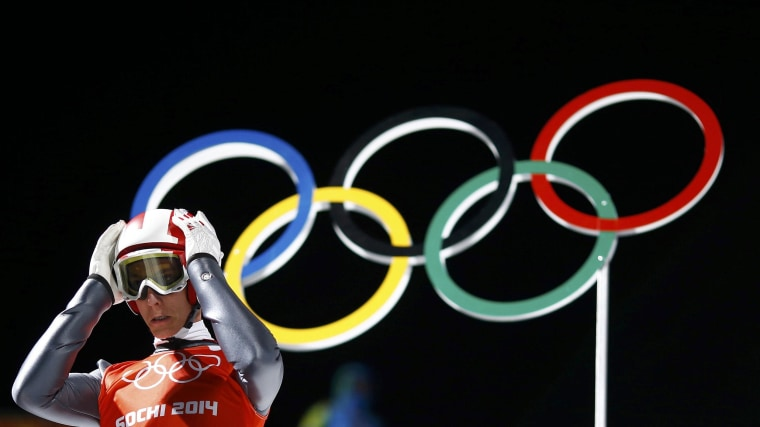 Image: Austria's Schlierenzauer adjusts his helmet as he prepares to jump during a training session for the men's ski jumping large hill individual event during the Sochi 2014 Winter Olympic Games
