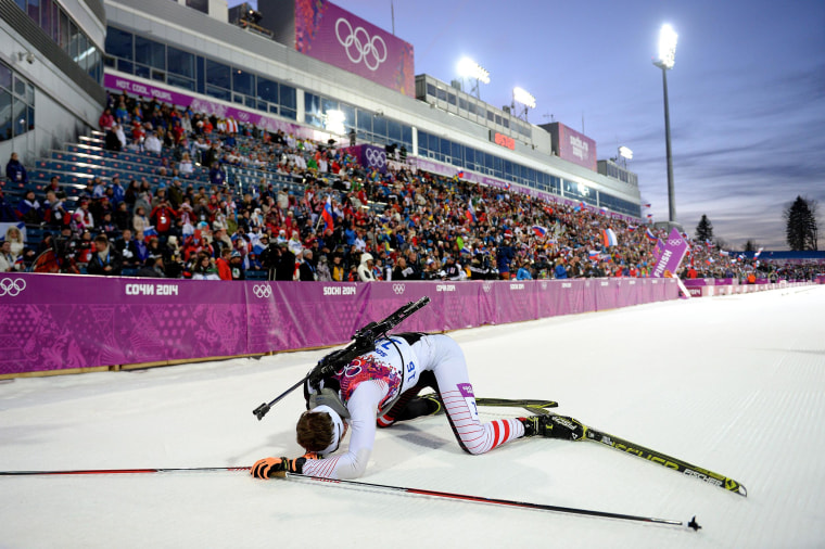 Image: Simon Eder of Austria collapses in the snow after the Men's Individual 20 km during day six of the Sochi 2014 Winter Olympics