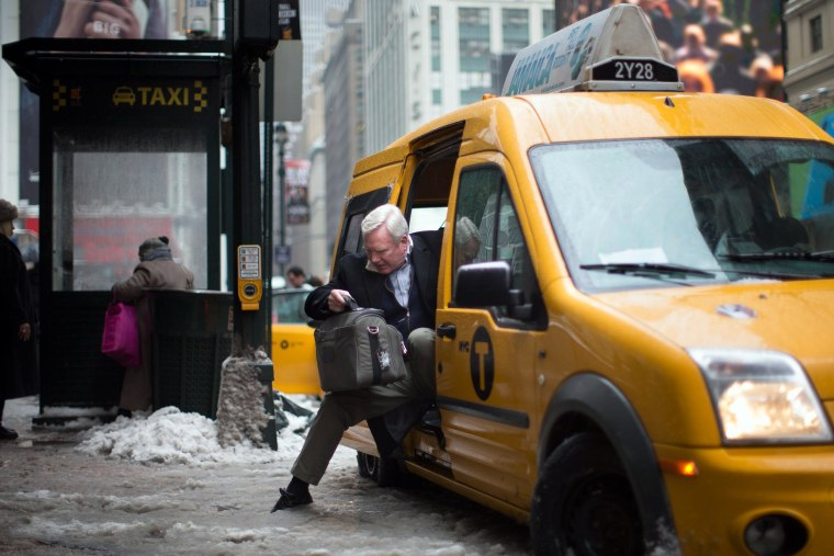 Image: A passenger struggles to exit his taxi over a slush puddle