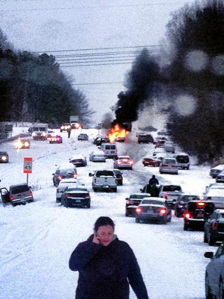 Image: A vehicle burns after it caught fire while struggling to get up a snow covered hill in Raleigh, N.C.