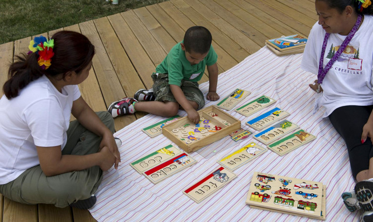 Lorena Arcos (left) and Jessica Castro (right), mothers trained by Chicago's Logan Square Neighborhood Association to advocate for early learning in their community, work with a boy from the neighborhood on his letters during an educational playgroup they helped organize.