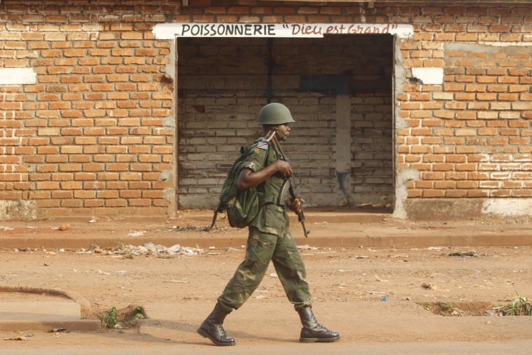 Image: A Democratic Republic of the Congo soldier, part of an African peacekeeping force, patrols beside a looted shop in Bangui