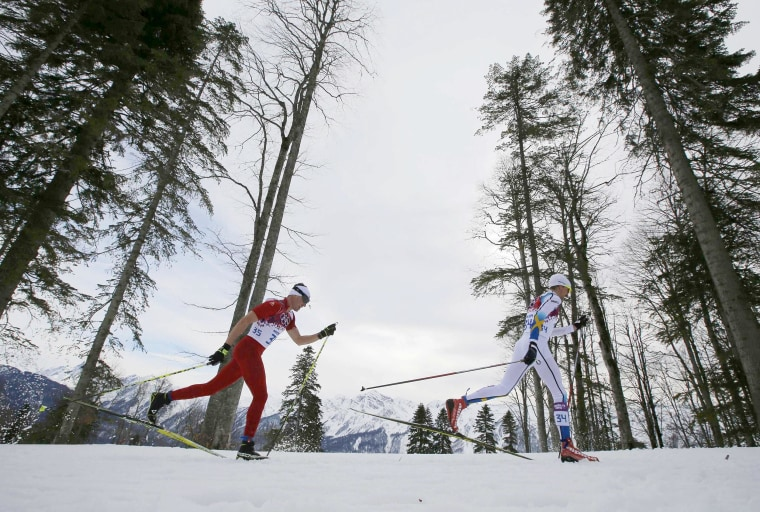Image: Switzerland's Cologna and Sweden's Olsson ski during men's cross-country 15km classic event at 2014 Sochi Winter Olympics