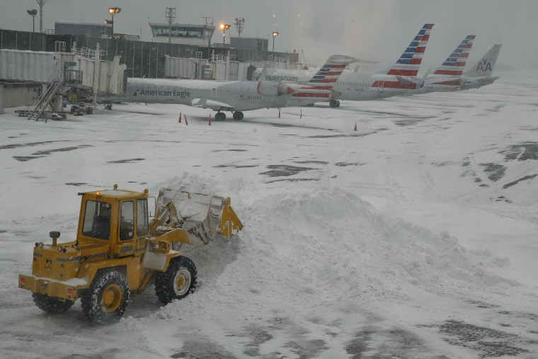 Bulldozer clears the gate areas of snow at LaGuardia Airport, New York. Another 1,600 flights were canceled on Friday on the East Coast.
