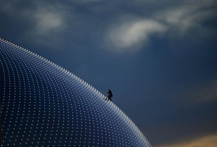 A person climbs on the Bolshoi Dome, one of the ice hockey venues, before the medals ceremony during the 2014 Sochi Winter Olympics on Feb. 14.