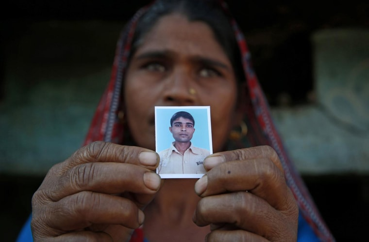 Image: Taravati, who uses only one name, shows a photograph Wednesday of her son Shiv Kumar Singh, a daily wage laborer, who was killed by a tiger at Maniawala, in northern India.