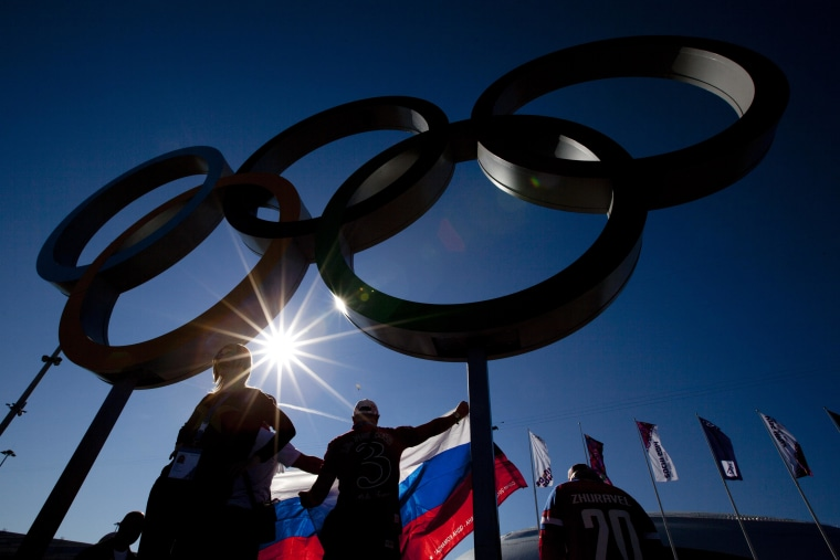 The Olympic Rings are silhouetted against the sun as people pose with a Russian flag during the 2014 Winter Olympics in Sochi, Russia, Thursday, Feb. 13, 2014. Temperature went up to around 15 degrees Celsius or 59 degrees Fahrenheit Thursday. (AP Photo/Peter Dejong)