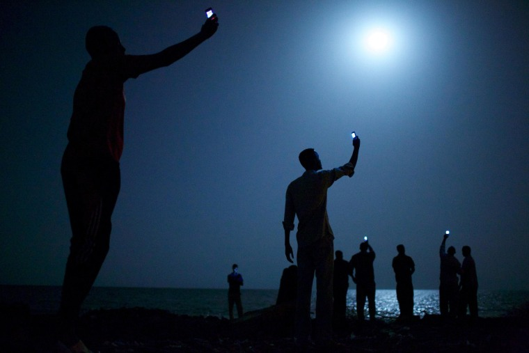 Image: African migrants on the shore of Djibouti city at night, raising their phones in an attempt to capture an inexpensive signal