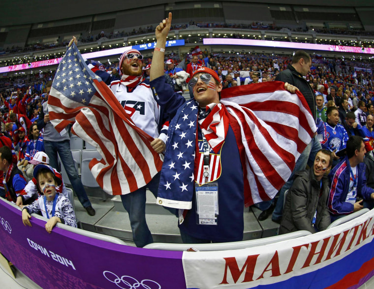 Fans of Team USA cheer before the men's preliminary round ice hockey game between Russia and Team USA at the 2014 Sochi Winter Olympics, February 15, 2014.