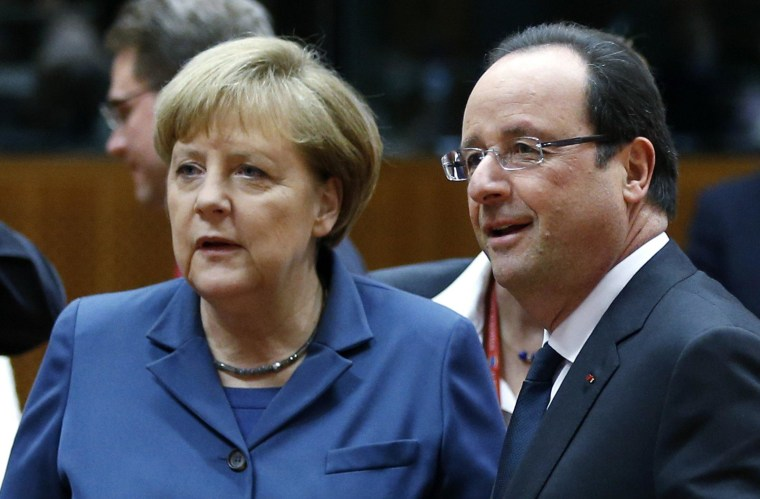 Image: Germany's Chancellor Merkel and France's President Hollande arrive at a EU leaders summit in Brussels