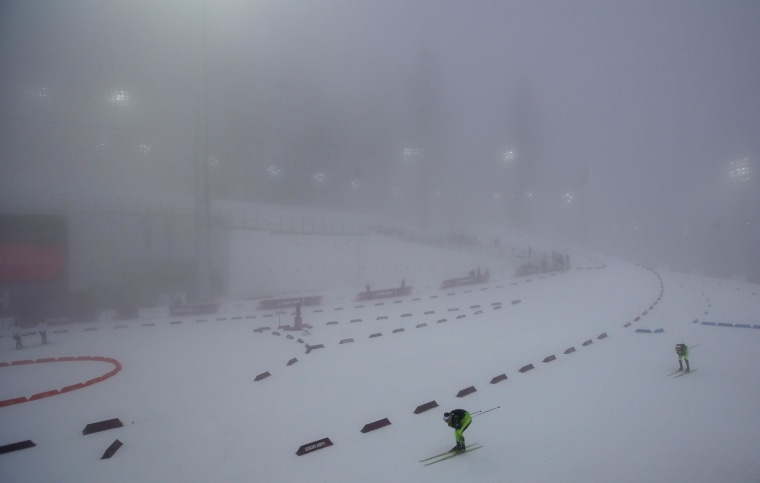 Image: Athletes ski through the fog as the men's biathlon 15K mass start race was postponed due to the lack of visibility at the 2014 Winter Olympics, Sunday, Feb. 16, 2014, in Krasnaya Polyana, Russia