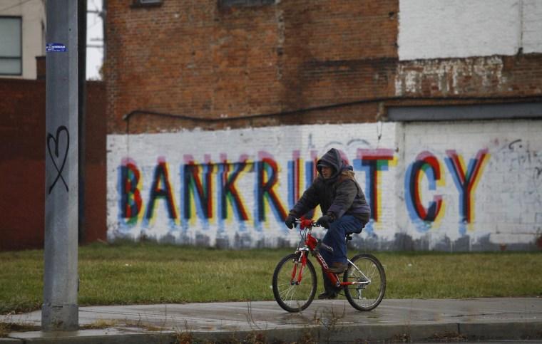 Image: A man rides his bike past graffiti in Detroit