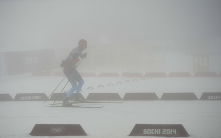 A Russian team's member skis as the Men's Biathlon 15 km Mass Start has been postponed for the second time due to bad weather condition at the Laura Cross-Country Ski and Biathlon Center during the Sochi Winter Olympics on Feb. 17, 2014, in Rosa Khutor, near Sochi.