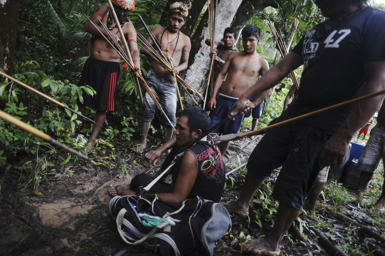 Munduruku Indian warriors stand guard over an illegal gold miner who was detained by a group of warriors searching out illegal gold mines and miners in their territory near the Caburua river, a tributary of the Tapajos and Amazon rivers in western Para state January 20, 2014. The Munduruku tribe has seen their land encroached on by wildcat miners in search of gold, and the tribe's leaders travelled to the capital Brasilia last year to demand the federal government remove non-indigenous miners from their territory. Rather than wait for a court decision to start the process - which could take years - the Munduruku decided to take matters into their own hands and expel the wildcat miners.