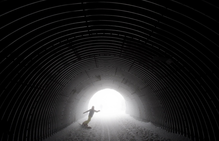 A snowboarder goes through a tunnel near the alpine skiing training slopes at the Sochi 2014 Winter Olympics on Feb. 17 in Krasnaya Polyana, Russia.