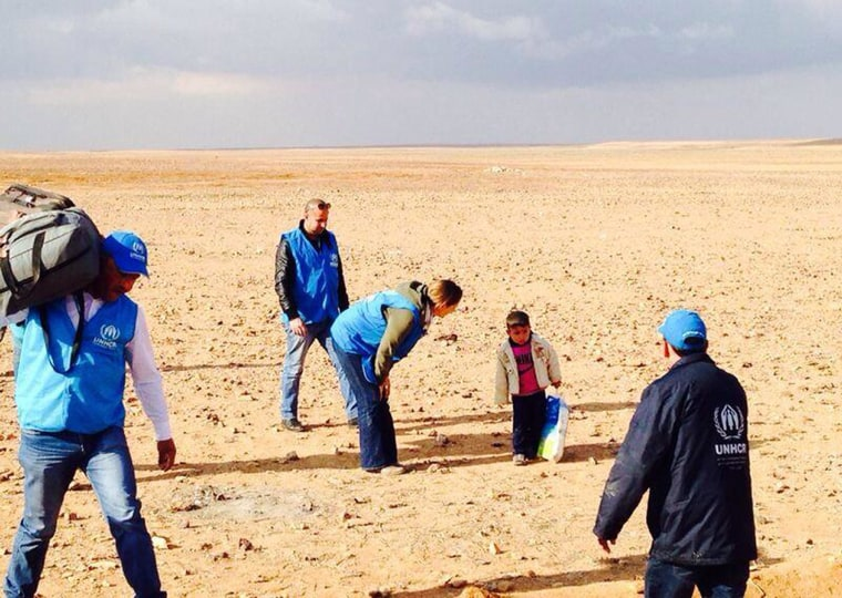 Marwan, a 4-year-old Syrian refugee who had been temporarily separated from his family, is assisted by UNHCR staff as he crosses the desert that straddles the Syrian border with Jordan.