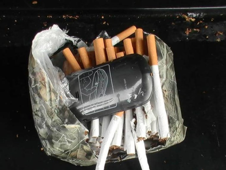 Image: A cellphone and cigarettes that were found inside a camouflage package near an undisclosed Florida state prison on Jan. 25, 2014.