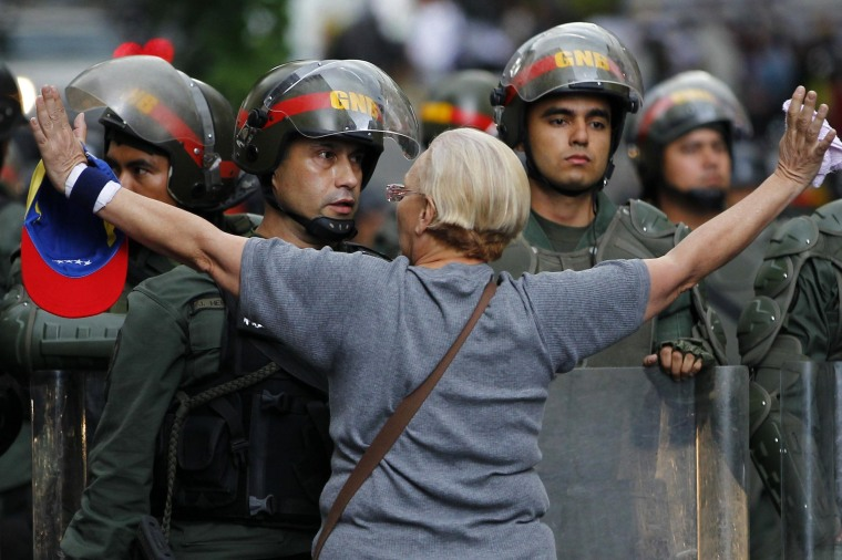 Image: An opposition supporter shouts at a riot police officer during a protest against President Nicolas Maduro's government in Caracas
