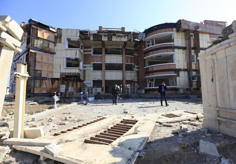 Image: People gather at the site of a bomb attack at a damaged building of the Ministry of Youth and Sport in Baghdad's Bayaa District