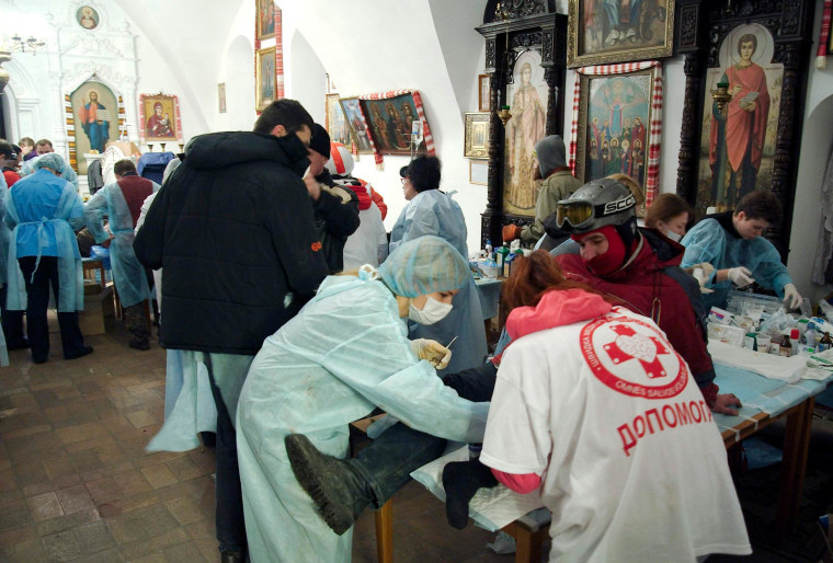 Image: Anti-government protesters receive medical treatment inside Mikhailovsky Zlatoverkhy Cathedral (St. Michael's golden-domed cathedral) in Kiev