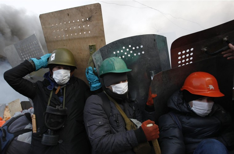 Image: Anti-government protesters take cover behind shields in Kiev on Wednesday