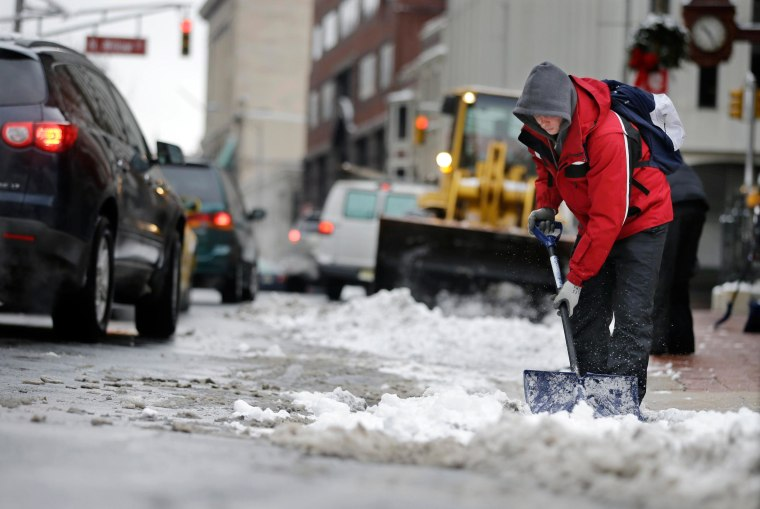 Workers clear newly-fallen snow from a street in Trenton, N.J..