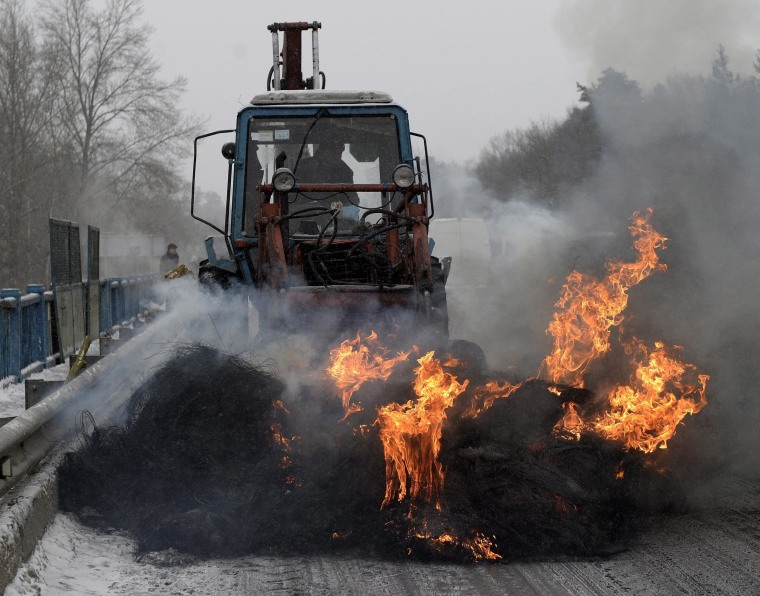 epa04041115 Burning tires are piled on the motorway to block the international route E40 in Nowojaworowsk in Ukraine, 25 January 2014. On the Ukrainian side the road leading from the border crossing Korczowa - Krakovets toward Lviv was blocked. The blockade is an expression of solidarity with the participants of anti-government protests on Independence Square in Kiev.  EPA/DAREK DELMANOWICZ POLAND OUT