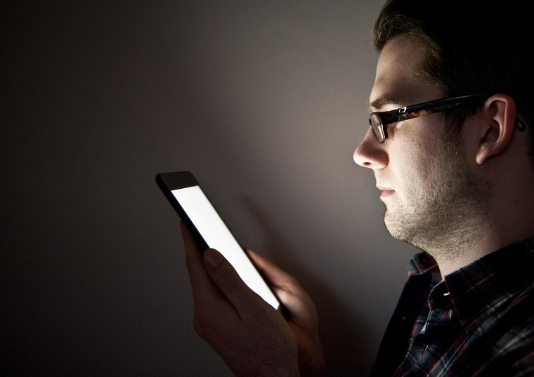 A man reads from an Apple iPad Mini tablet computer