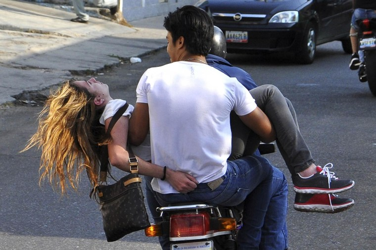 Image: Opposition supporter Genesis Carmona is evacuated on a motorcycle after being shot in the head during a protest against Nicolas Maduro's government in Valencia