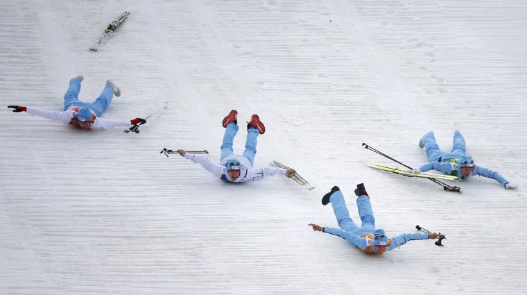 Image: Norway's team members slide after the flower ceremony for the Nordic Combined team Gundersen event of the Sochi 2014 Winter Olympic Games