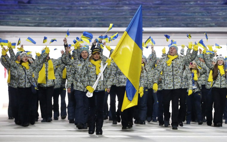 Valentina Shevchenko of Ukraine carries the national flag as she leads the team during the opening ceremony of the 2014 Winter Olympics in Sochi, Russia, Friday, Feb. 7, 2014.