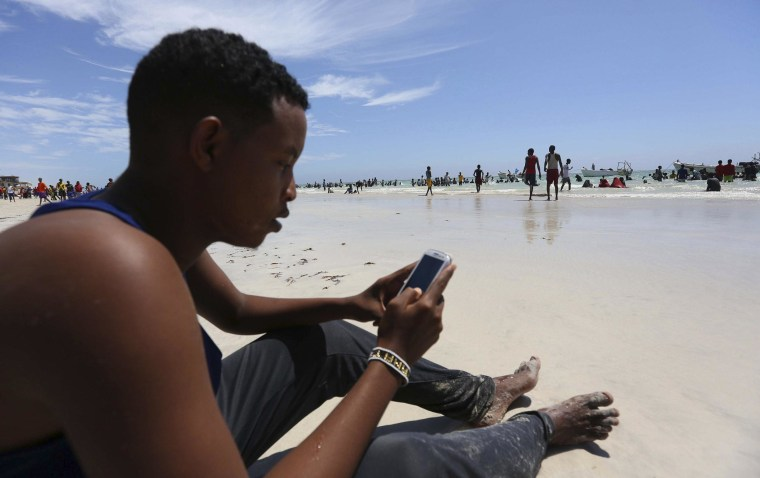 Image: A Somali man browses the internet on his mobile phone at a beach along the Indian Ocean coastline in Mogadishu