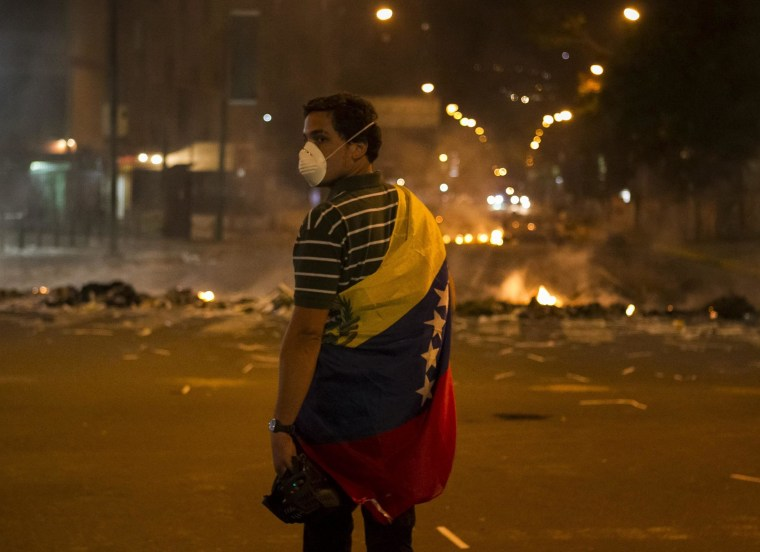 A man is wrapped in the Venezuelan flag as he stands close to a fire at a barricade during a protest against Venezuelan government in Altamira, Caracas, Venezuela, 20 February 2014.