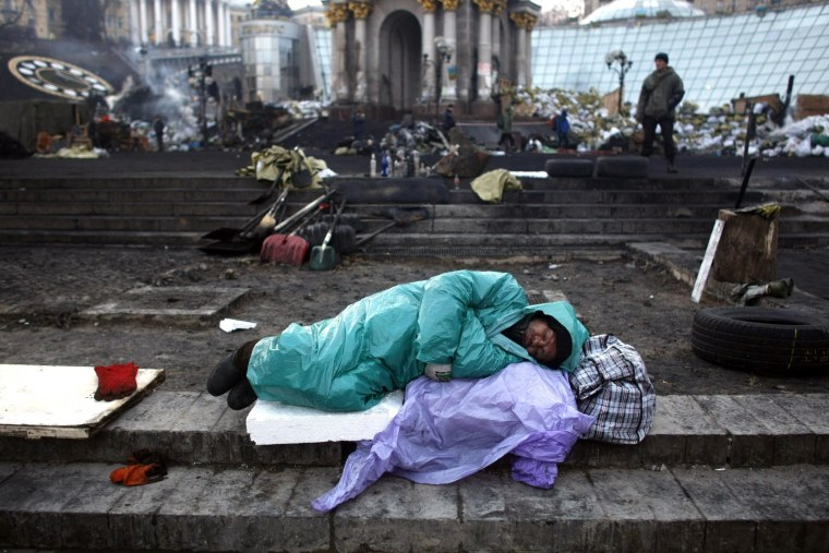 An anti-government protester sleeps at the Independence Square in Kiev, Ukraine, Friday, Feb. 21, 2014. Ukraine's presidency said Friday that it has negotiated a deal intended to end battles between police and protesters that have killed scores and injured hundreds, but European mediators involved in the talks wouldn't confirm a breakthrough. (AP Photo/ Marko Drobnjakovic)