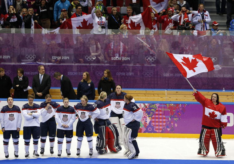 Canada's goalie Shannon Szabados (R) stands with her national flag near Team USA after Canada won their women's gold medal ice hockey game at the Sochi 2014 Winter Olympic Games February 20, 2014.