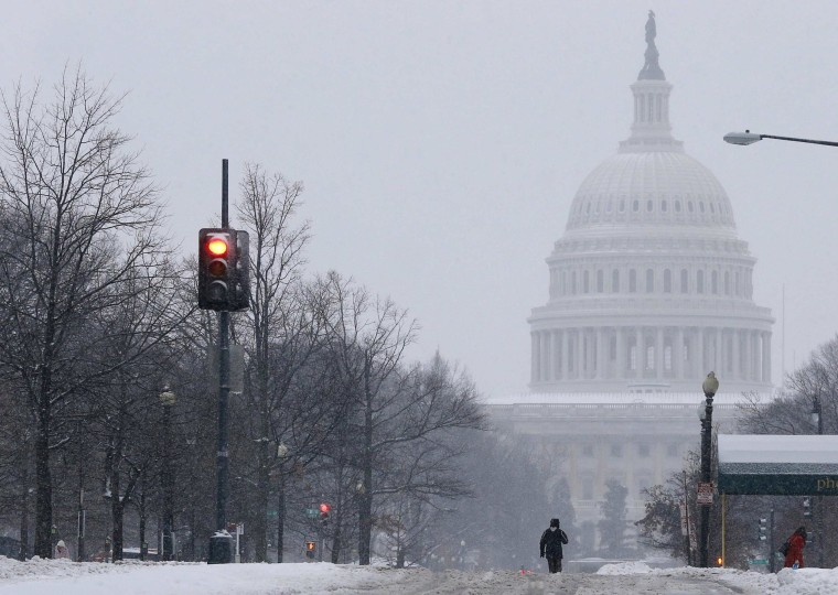 Image: A pedestrian walks up the middle of North Capitol Street towards the U.S. Capitol building in Washington