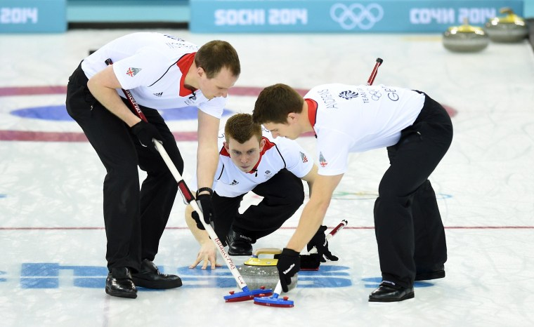 Great Britain's Scott Andrews and Michael Goodfellow brush the ice surface after Greg Drummond threw the stone during the Men's Curling Gold Medal Game between Canada and Great Britain at the Ice Cube Curling Center in Sochi during the Sochi Winter Olympics on Feb. 21, 2014.