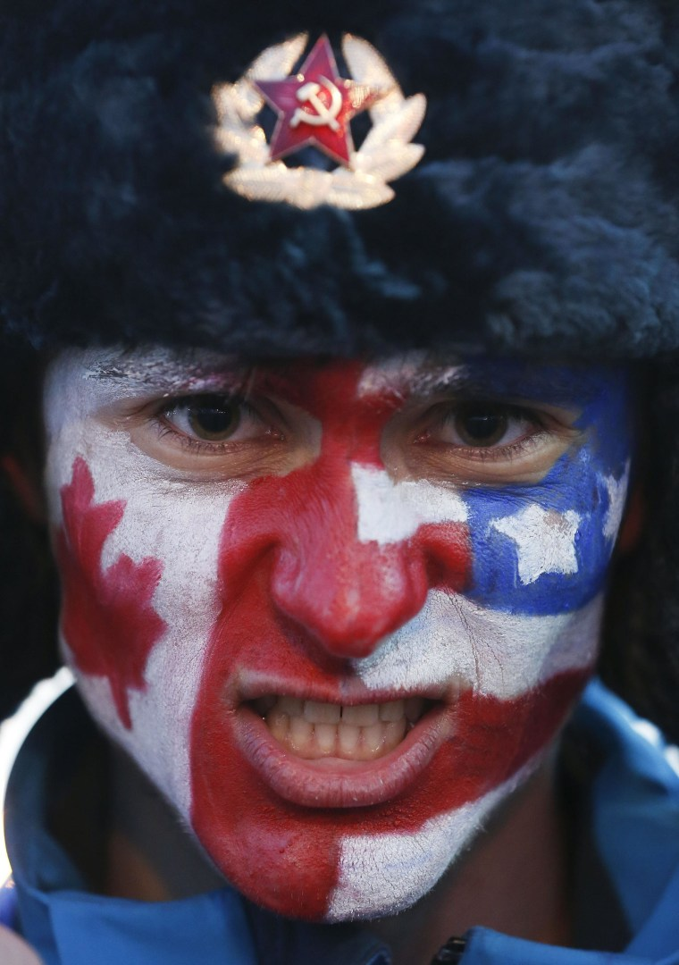 A hockey fan shows off the flags of Canada and the USA painted on his face before a semifinal men's ice hockey game between the two countries at the 2014 Winter Olympics on Friday.