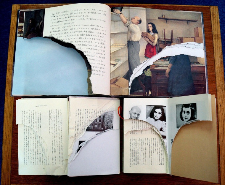 """Image: Ripped pages of Anne Frank's \""""Diary of a Young Girl\"""" are displayed at a library in Tokyo"""