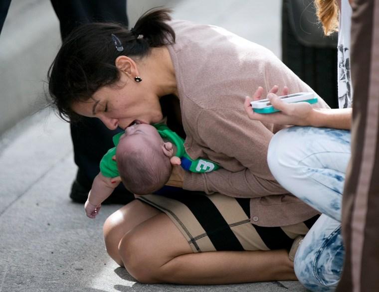 Image: Pamela Rauseo, 37, performs CPR on her nephew, five-month-old Sebastian de la Cruz