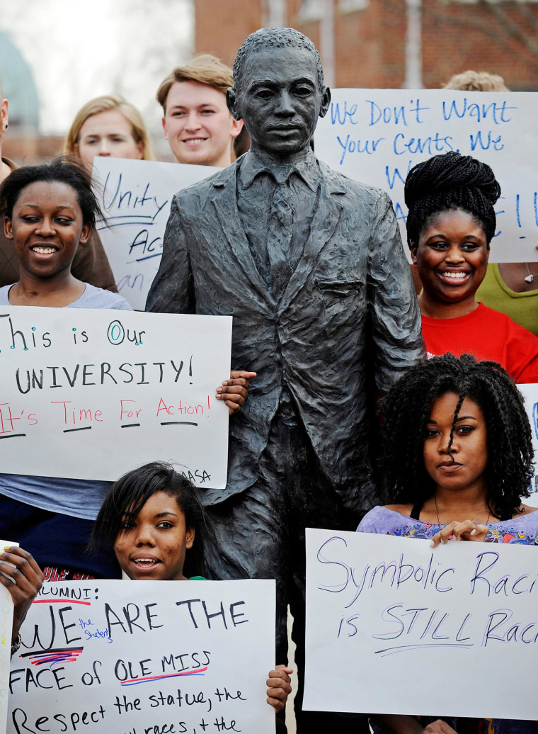 Image: Students hold signs while posing for a photo during a gathering in front of the James Meredith statue at the University of Mississippi