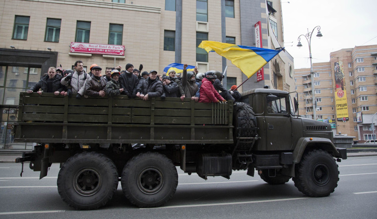 Image: Protesters ride atop of what appears to be a military truck in central Kiev, Ukraine