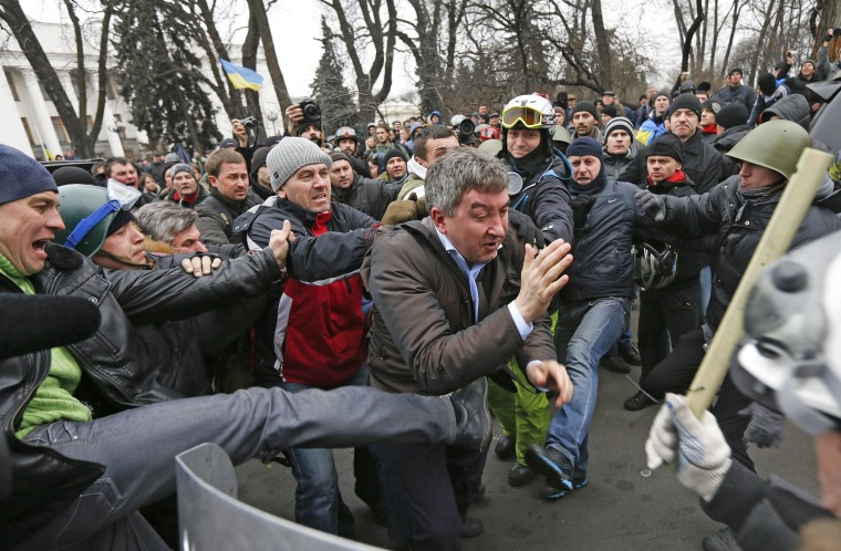 Anti-government protesters attack a deputy of the Party of Regions, Vitaly Grushevsky, outside the Ukrainian Parliament building in Kiev on Saturday. Downtown Kiev looked to be in the hands of the opposition on Saturday, after President Viktor Yanukovych made huge concessions to protesters and then left the city.