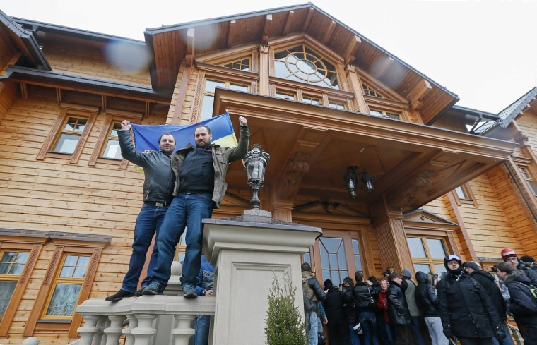 Ukrainians wave a national flag as they pose in front of the residence of Ukrainian President Viktor Yanukovych in the village of Mezhyhirya, near the capital Kiev on Saturday. Protesters took full control of the Yanukovych residence and opened the premises to the public and the media.