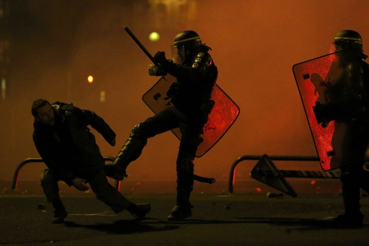 Image: A protester is kicked by a French CRS riot policman after clashes during a march in Nantes, western France