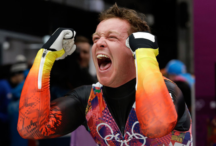 Image: Felix Loch of Germany celebrates after he crossed the finish area to win the gold medal during the men's singles luge final