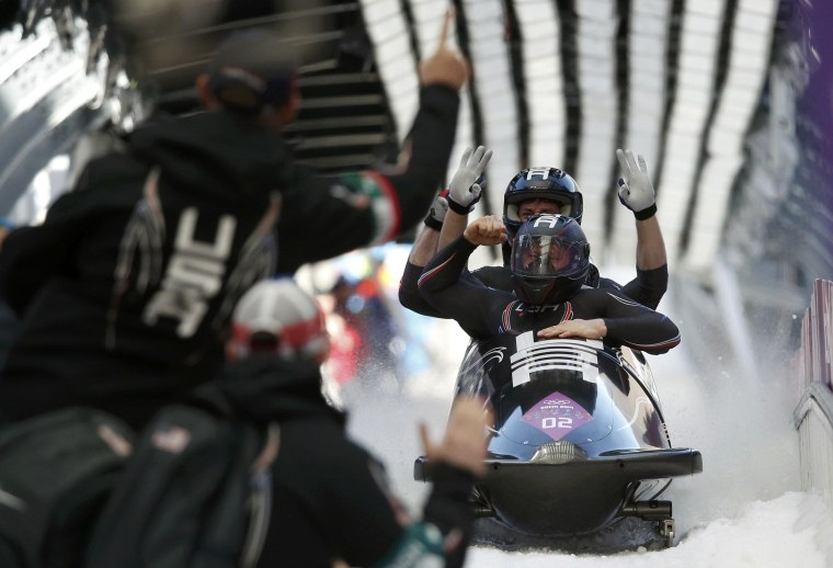 Image: Pilot Holcomb and his teammates of the U.S. react after a heat of the four-man bobsleigh event at the Sochi 2014 Winter Olympics