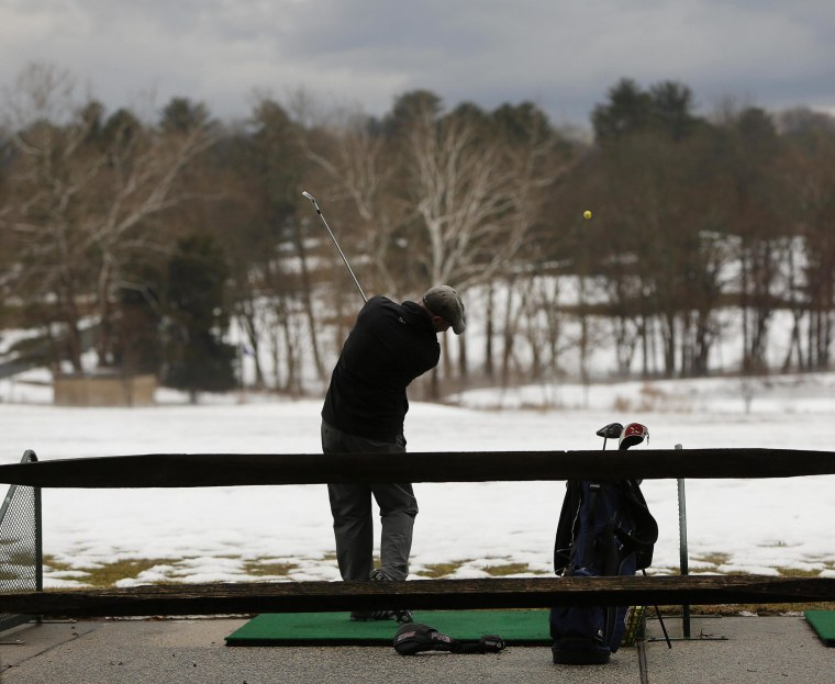 Image: Lone golfer works on his game under ominous skies at Northwest Golf Course in Silver Spring