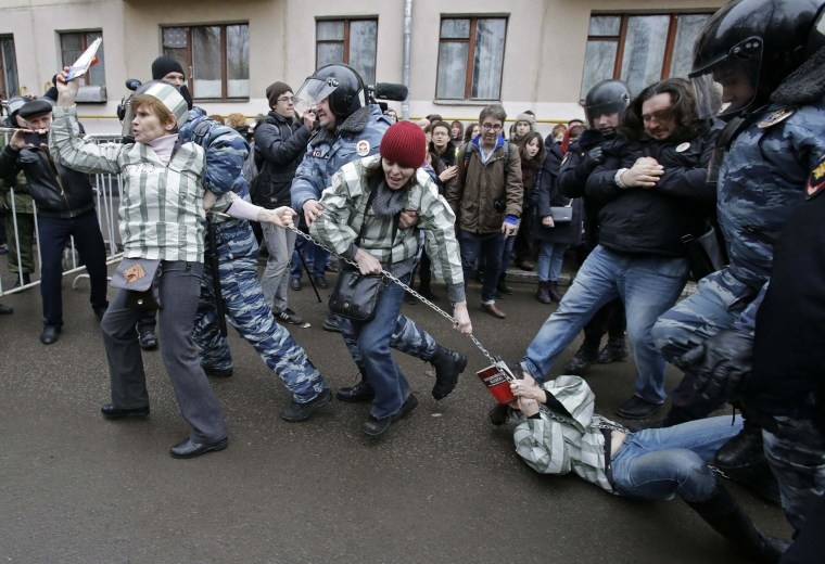 Police detain protesters outside a courthouse in Moscow February 24, 2014. Russian police detained dozens of protesters on Monday outside a Moscow courthouse where a judge was expected to sentence eight defendants convicted of attacking police at a 2012 demonstration against President Vladimir Putin.