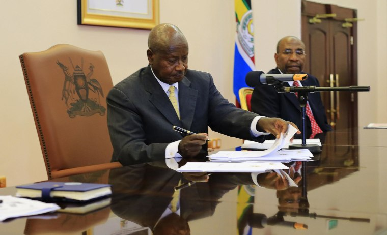 Image: Uganda President Yoweir Museveni signs an anti-homosexual bill into law at the state house in Entebbe